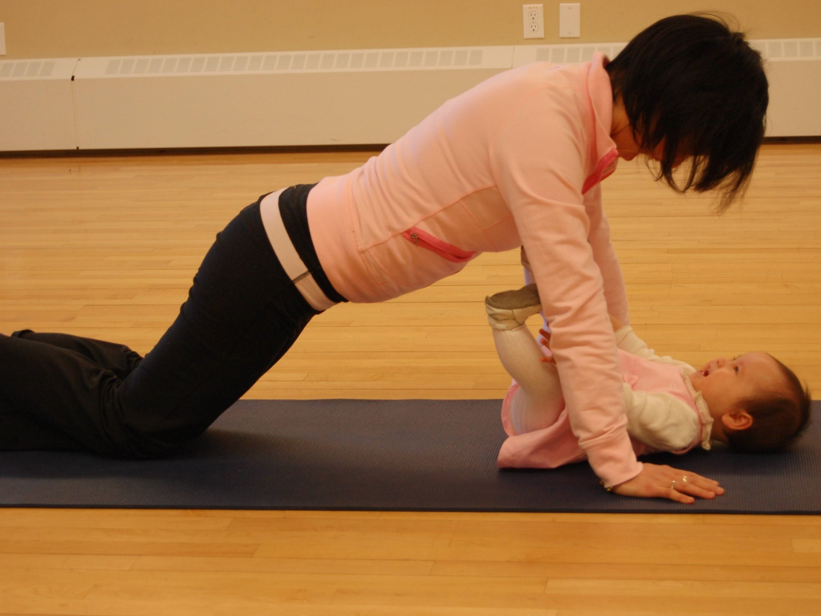 Woman doing yoga with baby